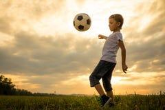 Młoda chłopiec bawić się w polu z piłki nożnej piłką Obrazy Stock