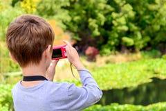 Młoda chłopiec bierze fotografie staw Zdjęcie Royalty Free