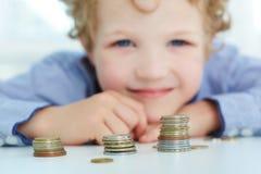 Młoda chłopiec budowa wierza monetami Fotografia Royalty Free