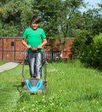 Młoda chłopiec ciie trawy z gazonu kosiarzem Zdjęcia Royalty Free