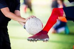 Młoda chłopiec gracz piłki nożnej kopnięcia piłka w rękach trener zdjęcie stock