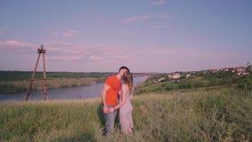 Młoda chłopiec i dziewczyna przychodzimy wpólnie, w centrum rama, buziak, most, rzeka, drzewa, trawa, natura, przeciw zbiory