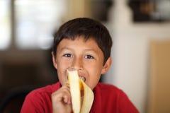 Młoda chłopiec je banana Fotografia Royalty Free