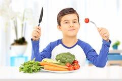 Młoda chłopiec je zdrowego posiłek sadzającego przy stołem Obrazy Royalty Free