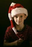 Młoda chłopiec jest ubranym kolorowego pasiastego Santa kapelusz Obraz Stock