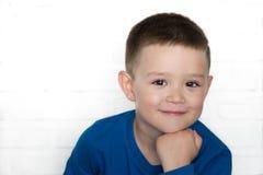 Młoda chłopiec jest ubranym niebieską marynarkę ono uśmiecha się patrzejący kamerę Fotografia Stock