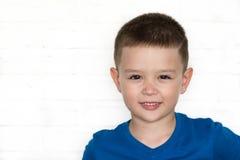 Młoda chłopiec jest ubranym niebieską marynarkę ono uśmiecha się podczas gdy patrzejący Zdjęcia Royalty Free
