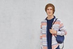 Młoda chłopiec jest ubranym przypadkowego koszulowego mienie plecaka na jego przeciw popielatej betonowej ścianie z kopii przestr Zdjęcia Royalty Free