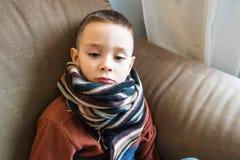 Młoda chłopiec jest ubranym pulower i szalika obsiadanie na kanapie Grypowy i sezonowy choroby pojęcie domowy traktowanie zdjęcia stock