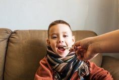 Młoda chłopiec jest ubranym pulower i szalika obsiadanie na kanapie z rozpieczętowanym usta Jego matka daje on medycynie Grypa i obraz royalty free