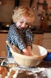 Młoda chłopiec która miesza mąkę Obrazy Royalty Free
