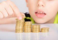 Młoda chłopiec liczy jego monety Obrazy Royalty Free