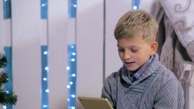 Młoda chłopiec mówić przez cyfrowej pastylki, białej Zdjęcie Royalty Free