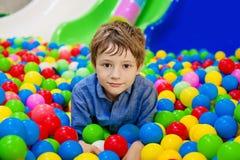 Młoda chłopiec ma zabawę bawić się z kolorowymi plastikowymi piłkami obraz royalty free