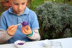 Młoda chłopiec maluje Wielkanocnych jajka plenerowych w Francja Wielkanocnych dzieci kreatywnie aktywność zdjęcia royalty free