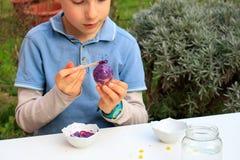 Młoda chłopiec maluje Wielkanocnych jajka plenerowych w Francja Wielkanocnych dzieci kreatywnie aktywność obraz royalty free