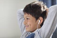 Młoda chłopiec ogląda komputer z hełmofonami Obrazy Royalty Free