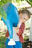 Młoda chłopiec opróżnia podlewanie puszkę Fotografia Stock