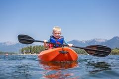 Młoda chłopiec paddling kajaka na pięknym halnym jeziorze Zdjęcie Royalty Free