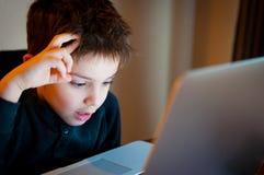 Młoda chłopiec patrzeje ekran komputerowego fotografia stock