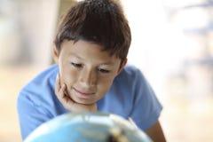 Młoda chłopiec patrzeje kulę ziemską Obrazy Royalty Free