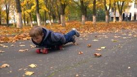 Młoda chłopiec próbuje jechać deskorolka na brzuchu zbiory