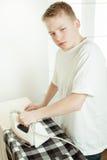 Młoda chłopiec prasowania koszula i Patrzeć Gderliwy obrazy stock