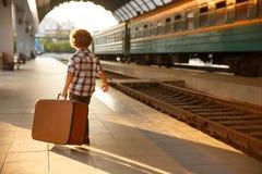 Młoda chłopiec przewożenia walizka w staci kolejowej obraz royalty free