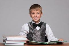 Młoda chłopiec przy biurkiem z książkami fotografia royalty free