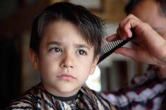 Młoda chłopiec przy fryzjera męskiego sklepem fotografia royalty free