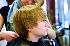 Młoda chłopiec przy fryzjerem fotografia stock