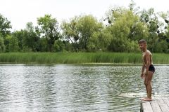 Młoda chłopiec przygotowywa skakać w jezioro, lato zabawa obraz stock