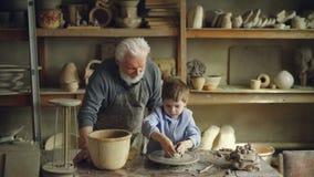Młoda chłopiec robi glinianej rzeźbie na garncarki ` s toczyć podczas gdy jego nauczyciel stoi blisko stołu daje on rada zbiory wideo