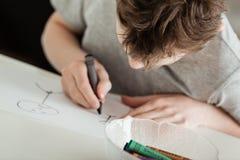 Młoda chłopiec Robi grafice Używać kredkę przy stołem Fotografia Stock