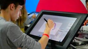 Młoda chłopiec rysuje na bardzo wielkiego komputeru pastylce zdjęcie wideo