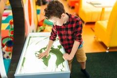Młoda chłopiec rysuje w piasku, rozrywki centrum Obrazy Royalty Free
