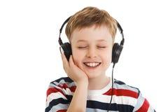 Młoda chłopiec słucha muzykę w hełmofony odizolowywający Obraz Stock