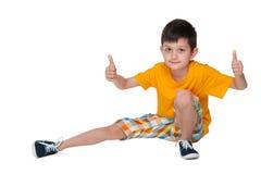 Młoda chłopiec siedzi jego aprobaty i trzyma fotografia stock