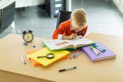 Młoda chłopiec siedzi przy biurkiem w biurze, chwyta magnifier fotografia royalty free