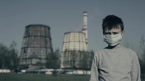 Młoda chłopiec stawia zanieczyszczenie maskę i patrzeć kamerę Przeciw Fabrycznym kominom Zanieczyszczenia powietrza poj?cie zbiory wideo