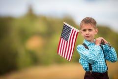 Młoda chłopiec trzyma flaga amerykańską Zdjęcia Stock