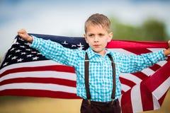 Młoda chłopiec trzyma flaga amerykańską pokazuje patriotyzm dla jego swój kraju, Jednoczy stany Fotografia Royalty Free
