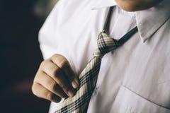 Młoda chłopiec trzyma jego krawat, krawat/ Zdjęcia Stock