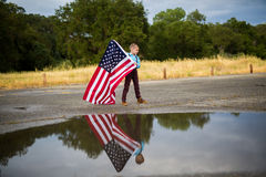 Młoda chłopiec trzyma wielką flaga amerykańską pokazuje patriotyzm dla jego swój kraju, Jednoczy stany obrazy royalty free