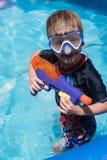 Młoda chłopiec trzyma wodnego pistolet w pływackim basenie w pływanie masce zdjęcia stock