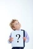 Młoda chłopiec trzyma znaka zapytania znaka odizolowywający na białym tle Zdjęcia Stock