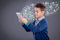Młoda chłopiec używa pastylkę, szkolnego uczenie lub technologii pojęcie, Zdjęcia Royalty Free