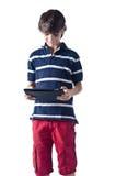 Młoda chłopiec używa pastylka komputer. Odosobniony. zdjęcia royalty free