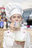 Młoda chłopiec ubierał jako szef kuchni pije herbaty w kuchni Fotografia Royalty Free