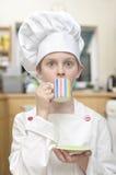 Młoda chłopiec ubierał jako szef kuchni pije herbaty w kuchni Fotografia Stock